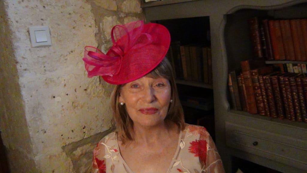 Older woman wearing a bright pink wedding fascinator