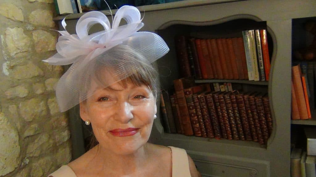 Pale pink net or crin fascinator worn by an older woman for a wedding