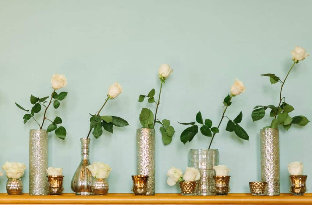 Simple home wedding floral display of white roses in silver vases