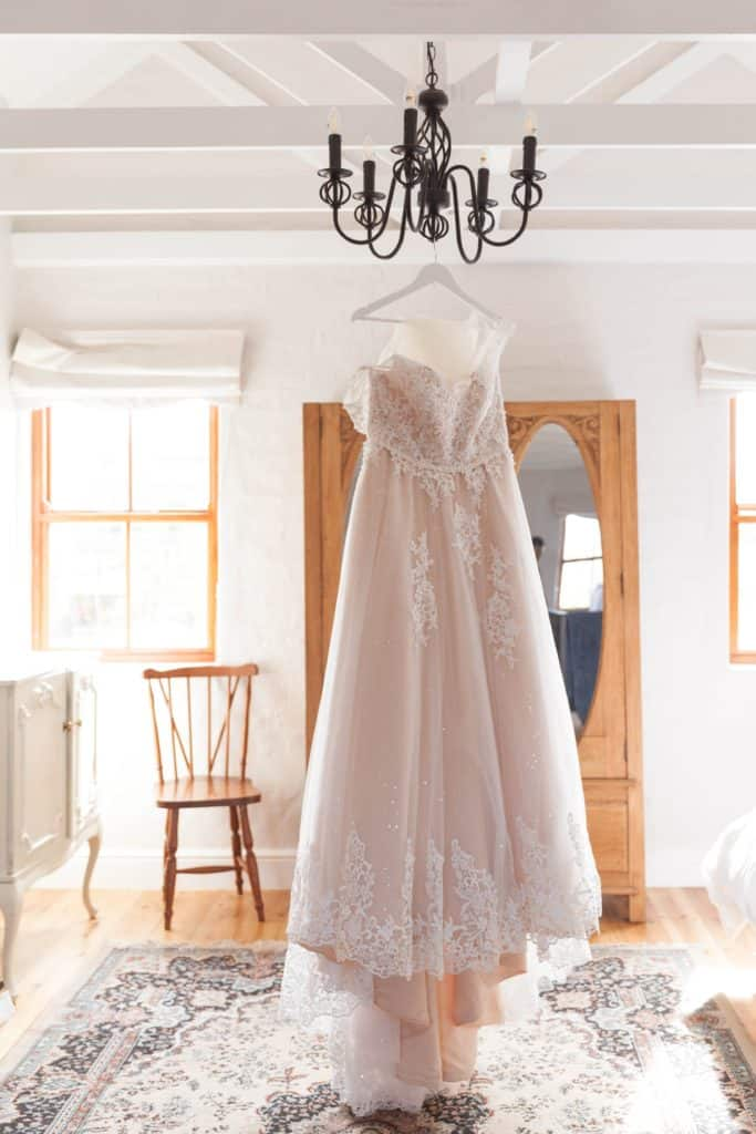 A bridal dress hanging up in a home bedroom