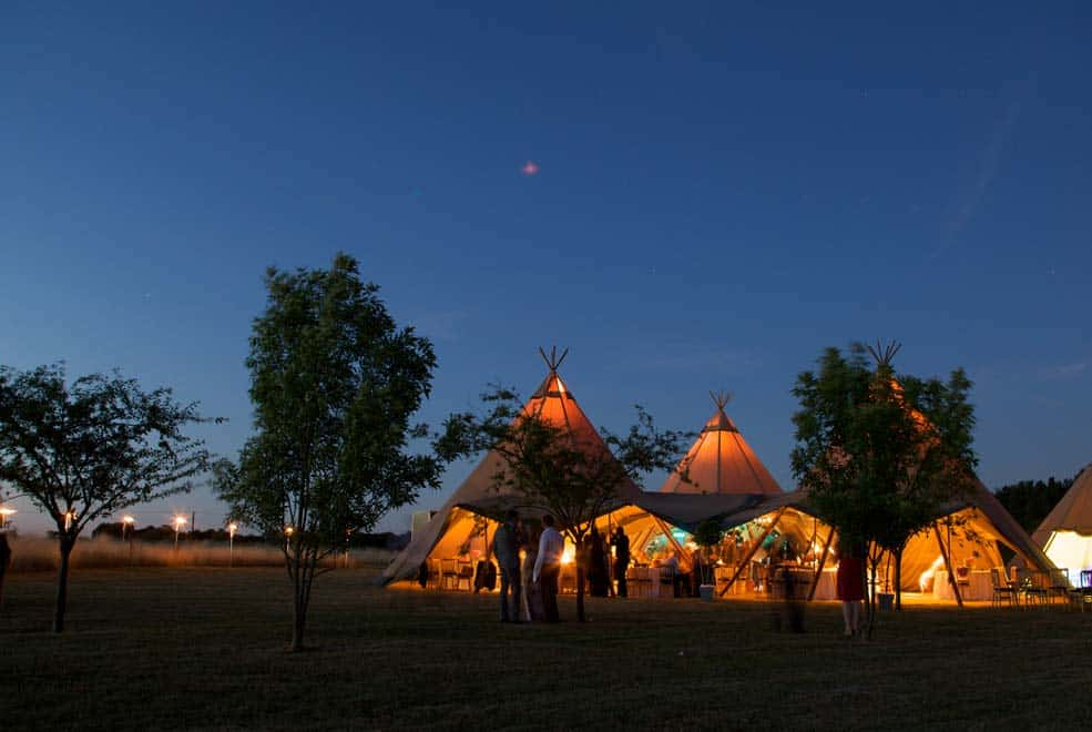 Several linked tipis host a wedding party at night