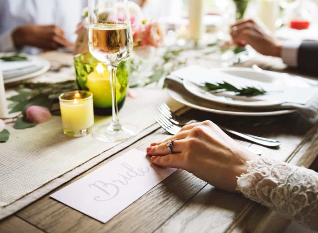 The bride's hand shows her ring as she sits at the wedding table