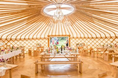 Interior of yurt with tables and bench seats for wedding guests
