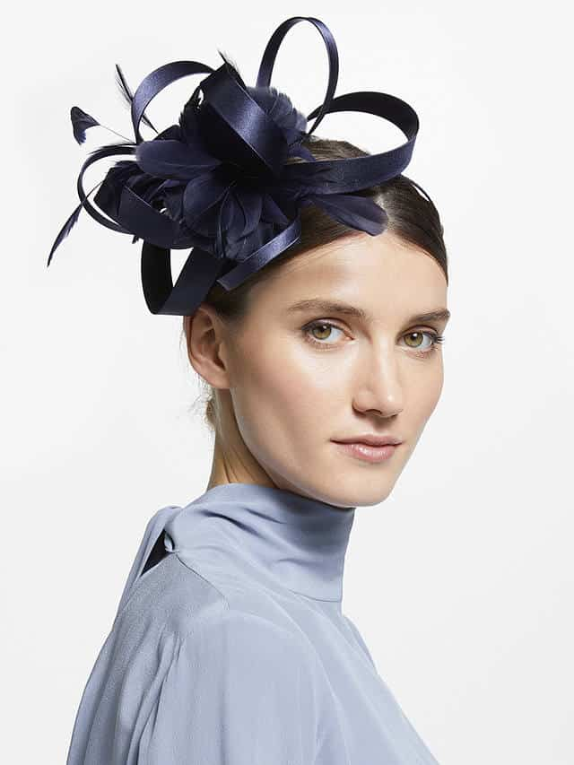 A ribbons and feathers fascinator in navy worn with neatly tied back hair is ideal for a Spring wedding.