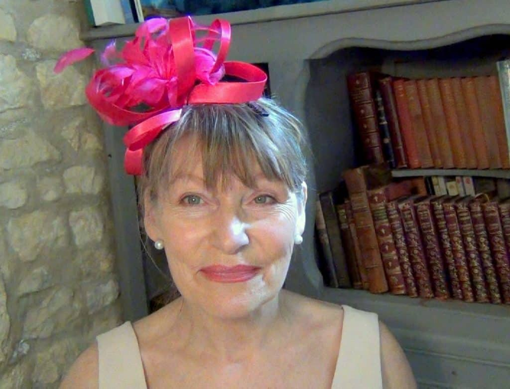 Bright pink ribbon fascinator worn by older woman for a wedding