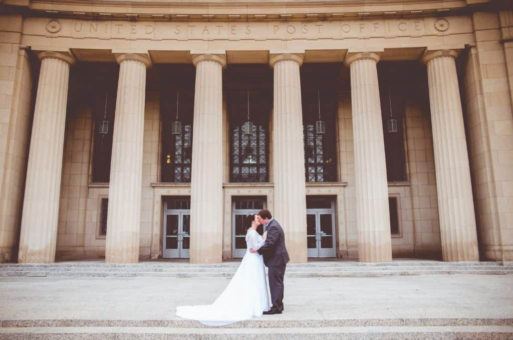 Bride and groom kiss outside the grand facade of the US Post Office