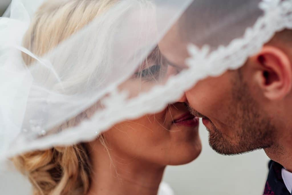 The groom kissing the bride beneath her veil