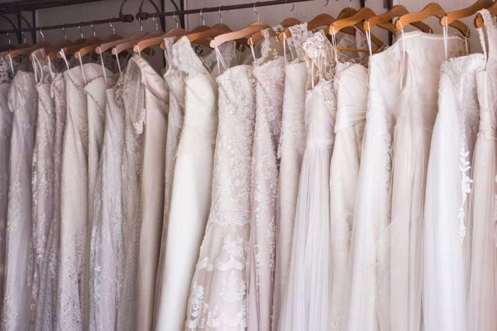 Lots of wedding dresses hanging up in a store