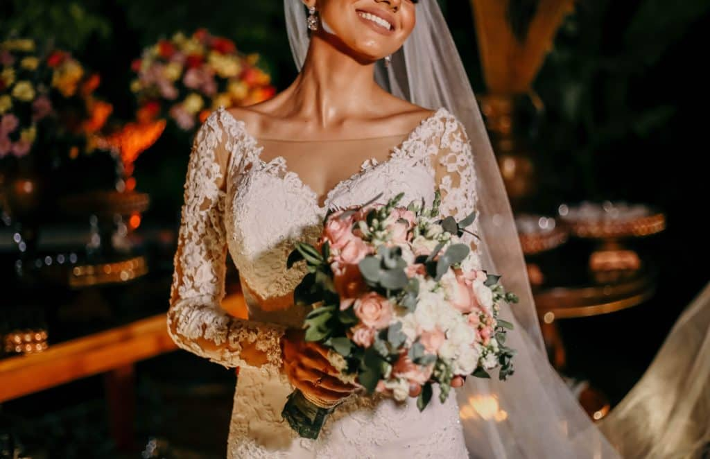 A smiling bride in white walks down the aisle