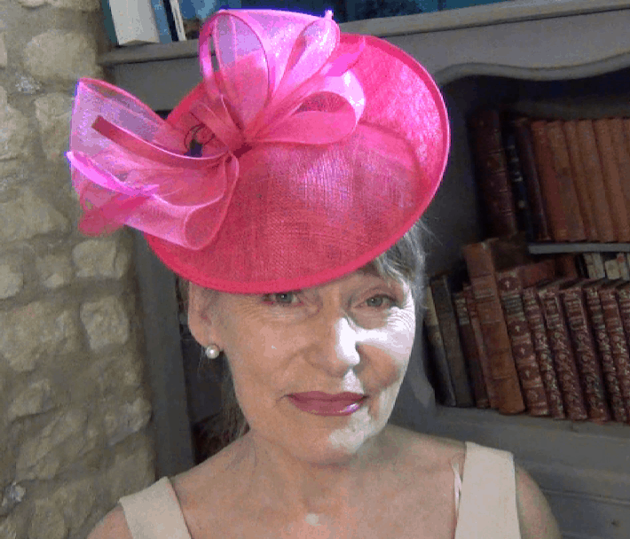 Older lady trying on bright pink wedding hat
