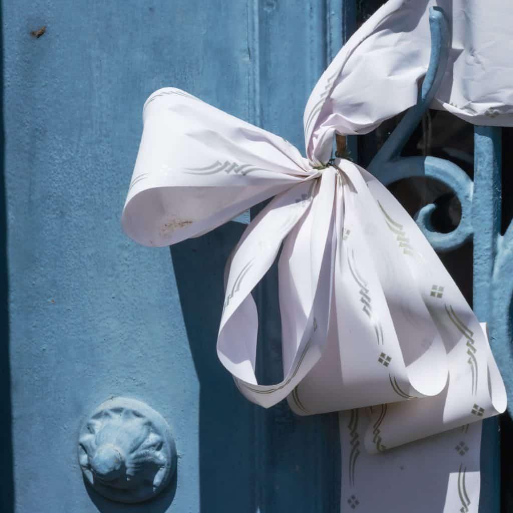 A wedding ribbon on a blue metal gate