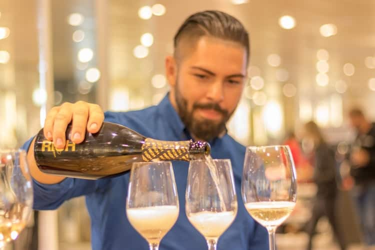 Bartender or wine waiter pours drinks at a wedding