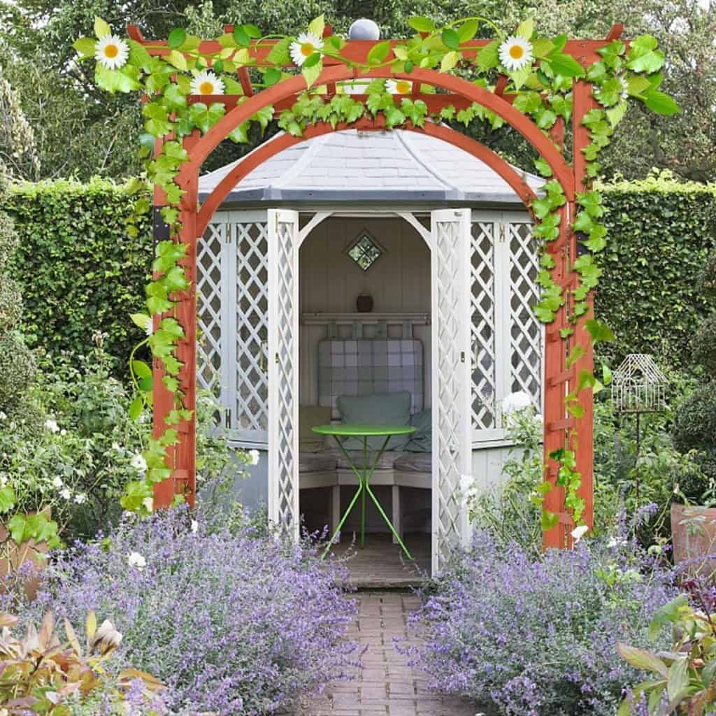 A wooden wedding arch decorated with climbing foliage and flowers stands outside the garden room used for the signing