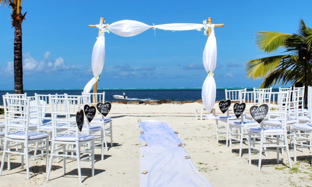 A simple bamboo arch is draped with tulle to frame the horizon at a beach wedding