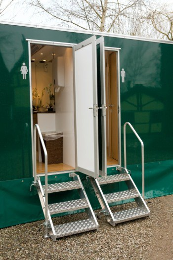 Two mobile toilets with steps up finished in dark green externally