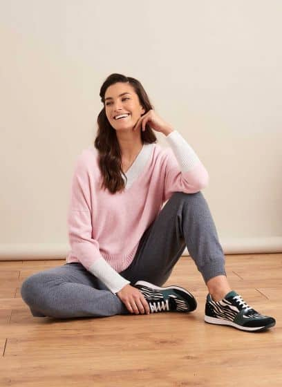 Girl sitting on floor wearing Brora grey cashmere joggers, grey trainers and large pink jumper