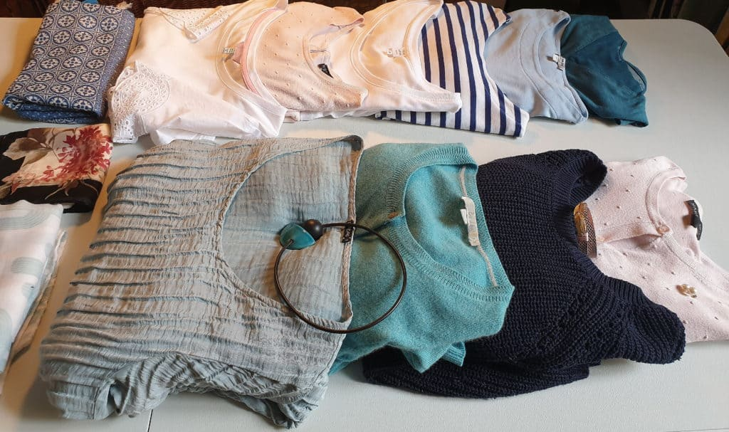 Capsule wardrobe tops in colors that complement your base color.  Here re white punk blue and green tops and layers.