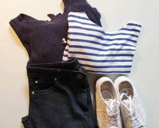 Capsule items with dark wash jeans, breton tee, navy jumper and white sneakers
