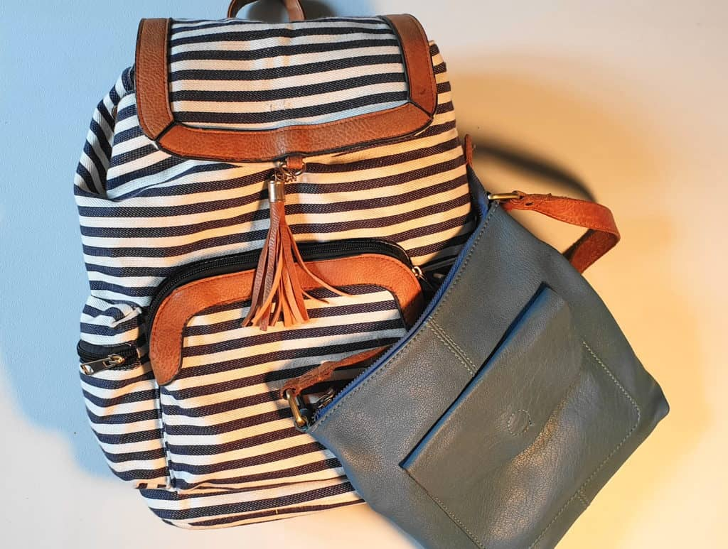 Two bags for your blue capsule wardrobe - one cross-body bag and one larger striped backpack