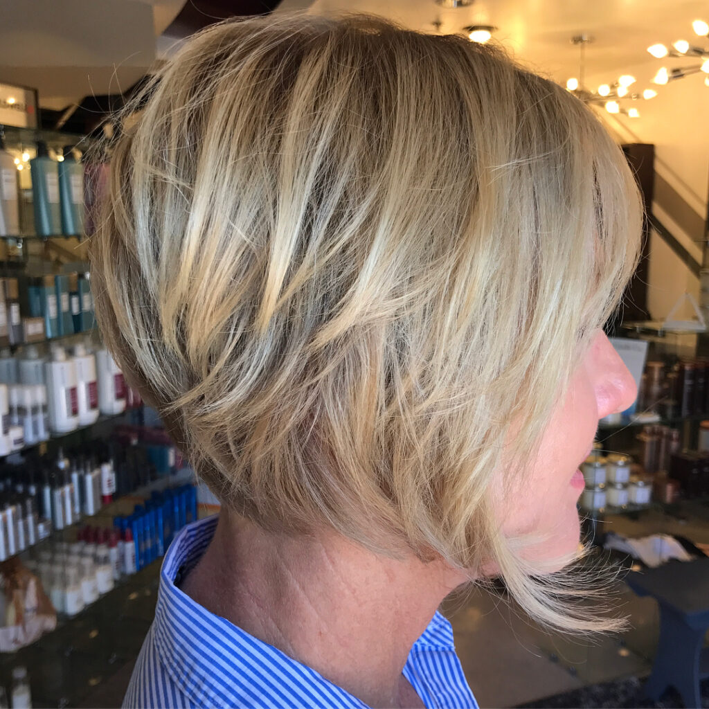 Over 50 hairstyle blonde highlighted layered bob with long bangs