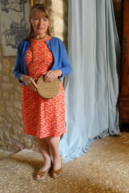 Orange printed dress by Boden with tan platforms and woven bag