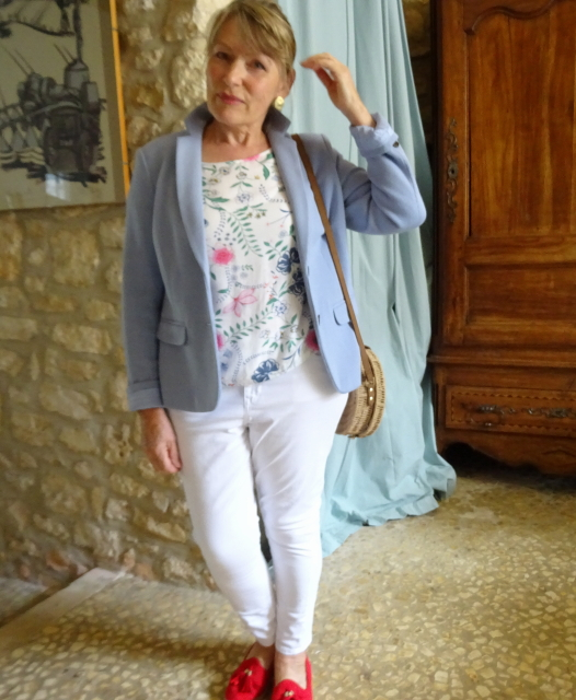 Mid blue jacket over narrow white jeans and a floral top