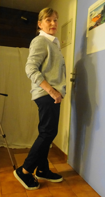 Black trousers and trainers with a cashmere cardigan in grey