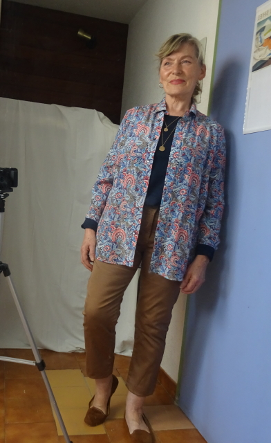 Blue Liberty print patterned silk shirt by Brora over navy too and tan pants