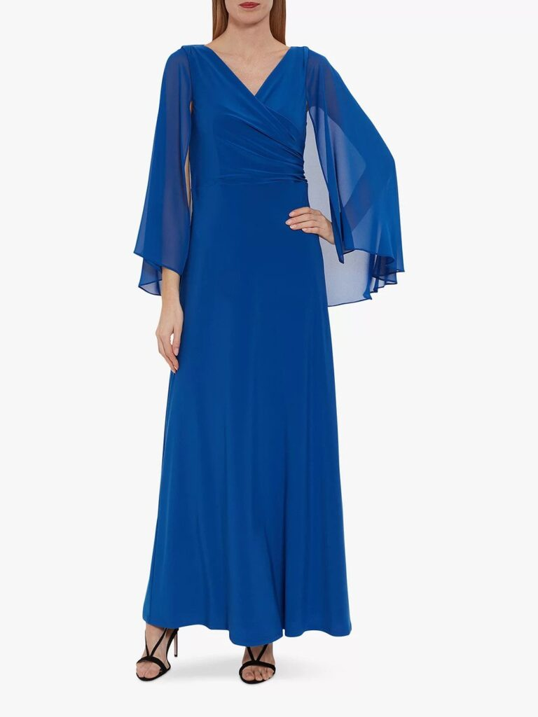 A floor length formal gown in strong blue with a sheer ble cape attached by Gina Bacconi at John Lewis